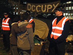 © licensed to London News Pictures. London, UK. 14/07/12. Two activists comfort one another looking past bailiffs into the campsite. Enforcement officers clear the remaining 'Occupy' protest camp in London's Finsbury Square during the early hours of this morning after Islington Council won a High Court battle over the site. Photo credit: Jules Mattsson/LNP