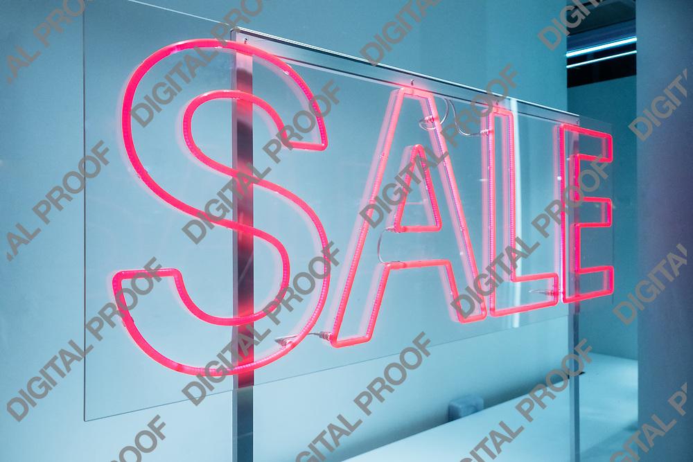 Zurich, Switzerland - December 22, 2018 A sale pink neon sign in an empty store with blue lights