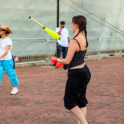 Baltimore, MD, USA - June 16, 2012: A woman juggler entertains visitors at Inner Harbor in Baltimore, MD.
