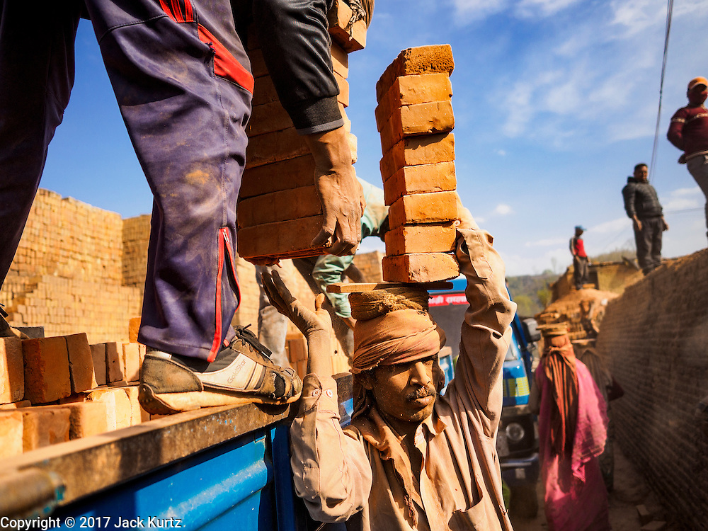03 MARCH 2017 - BAGMATI, NEPAL: Workers deliver bricks to a waiting truck at a brick factory in Bagmati, near Bhaktapur. There are almost 50 brick factories in the valley near Bagmati. The brick makers are very busy making bricks for the reconstruction of Kathmandu, Bhaktapur and other cities in the Kathmandu valley that were badly damaged by the 2015 Nepal Earthquake. The brick factories have been in the Bagmati area for centuries because the local clay is a popular raw material for the bricks. Most of the workers in the brick factories are migrant workers from southern Nepal.       PHOTO BY JACK KURTZ