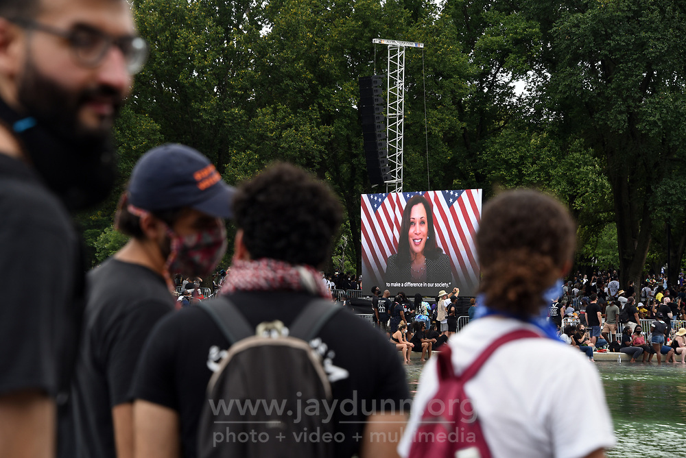 """US Senator and Democratic vice presidential nominee Kamala Harris delivers a prerecorded speech to a hushed crowd at the Lincoln Memorial. On Friday, August 28th, 2020, thousands of people from all over the country attended the Commitment March in Washington, D.C.to fight for criminal justice reform in solidarity with those who have lost loved ones at the hands of the police and to push for federal legislation against misconduct. The event, organized by the Reverend Al Sharpton and the National Action Network under the rallying call 'Get Your Knee Off Our Necks,' coincides with and honors the 57thanniversary of Martin Luther King, Jr.'s March on Washington, where he delivered his historic """"I Have A Dream"""" speech in 1963. Photograph by Jay Dunn."""