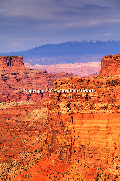 A view of red-rock canyons overlooking the Colorado River with the LaSal Mountains in the distant background, as seen from near the visitor center at Canyonlands National Park, Utah. WATERMARKS WILL NOT APPEAR ON PRINTS OR LICENSED IMAGES.<br /> <br /> Licensing: https://tandemstock.com/assets/47663446