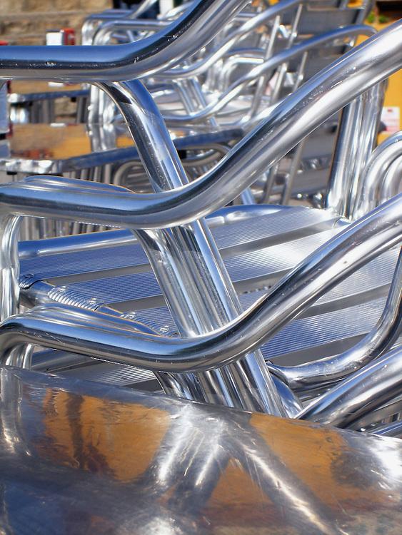 Sillas de bar de aluminio apiladas. Calle Betis, Sevilla. / Aluminum stacked up chairs. Seville. Spain