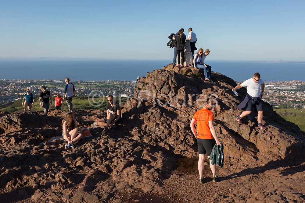 Walkers enjoy summer evening sunshine on the summit of Arthurs Seat in Holyrood Park, overlooking the city of Edinburgh and the Firth of Fourth estuary, on 26th June 2019, in Edinburgh, Scotland. Arthurs Seat is an extinct volcano which is considered the main peak of the group of hills in Edinburgh, Scotland, which form most of Holyrood Park, described by Robert Louis Stevenson as a hill for magnitude, a mountain in virtue of its bold design. The hill rises above the city to a height of 250.5 m 822 ft, providing excellent panoramic views of the city and beyond.