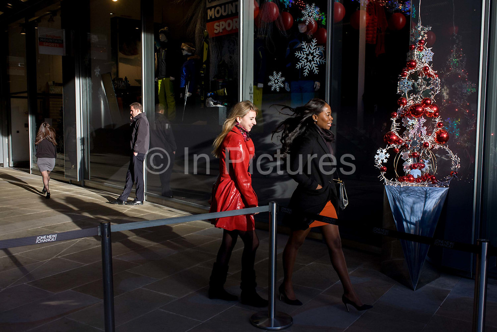 Wwo women shoppers walk through a City of London mall whose decorations feature a decorative Christmas tree and window ice patterns. The ladies walk betwen it and a barrier one lunchtime.