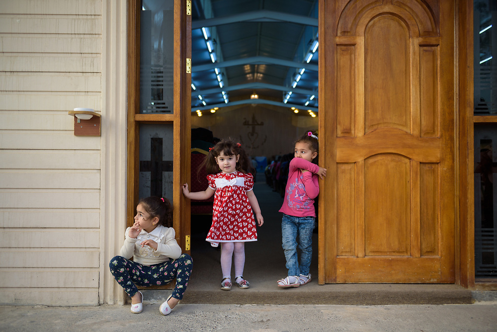 Three girls hang out in the doorway during a service at Mart Shmoni church, a Syriac Catholic church in Ankawa, a suburb of Erbil, Iraq. Most of the parishioners are IDPs, pushed out of their homes in Qaraqosh during the 2014 ISIS advance. (May 2, 2017)
