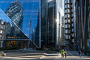 While office workers largely remain at home in accordance to government Covid guidelines and individual corporate policies, two security personnel patrol the plaza beneath insurance institutions, including Lloyds of London, on Leadenhall in the City of London, the capitals financial district, during the third lockdown of the Coronavirus pandemic, on 9th March 2021, in London, England.