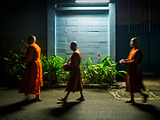 13 JANUARY 2019 - NAKHON PATHOM, THAILAND: Female monks from Wat Songdhammakalyani walk through the darkness on their early morning alms rounds. The Sangha Supreme Council, Thailand's governing body of Buddhist monks, bans the ordination of female monks, but hundreds of Thai women have gone abroad, mostly to Sri Lanka and India, to be ordained. There are about 270 women monks in Thailand and about 250,000 male monks. There are 7 monks and 6 novices at Wat Songdhammakalyani in Nakhon Pathom. It was the first temple in Thailand to have female monks. The temple opened 60 years ago and has always been a temple of women monks. Women can be ordained as novices in Thailand, but to be ordained as a full monk would require the participation of 10 female monks and 10 male monks, and male monks in Thailand are barred from participating in women's ordination ceremonies.    PHOTO BY JACK KURTZ