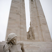 The female mourner sculpture in front of the twin white pylons of the Canadian National Vimy Memorial dedicated to the memory of Canadian Expeditionary Force members killed in World War one. The monument is situated at a 100 hectare preserved battlefield with wartime tunnels, trenches, craters and unexploded munitions. The memorial designed by Walter Seymour Allward opened in 1936.