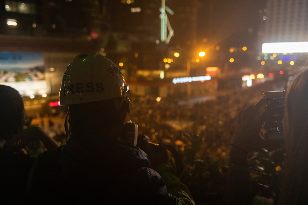 """Hong Kong - August 18, 2019: Journalists, including one wearing a face respirator and a hard hat marked """"Press"""", look down on a crowd of protestors in Hong Kong."""
