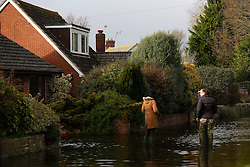 © Licensed to London News Pictures. 06/01/2014, Christchurch, UK. Residents talk outside their flooded houses at Burton, Christchurch, England , Monday, Jan. 6, 2014. Part of UK continue to be affected by floods and strong wind. Photo credit : Sang Tan/LNP