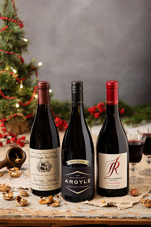 Festive still life of 3 Pinot Meunier bottles in holiday styled setting. Argyle, Irvine & Roberts, and Eyrie Vineyards all produce Pinot Meunier.