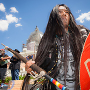 """Carrie Sage Curley, San Carlos Apache, dances to music played by fellow members of the San Carlos Apache Tribe as a demonstration was held in front of the United States Capitol to protest the transfer of Apache land to a private Australian-British mining corporation.  In December 2014, a rider to the National Defense Authorization Act handed over Oak Flat to a foreign-owned company looking to mine copper.  The Apache are currently """"occupying"""" Oak Flat, and travelled to D.C. to protest the action.  In response, Rep. Raul Grijalva (D-AZ-3), proposed the Save Oak Flat Act (H.R. 2811) in June, 2015 to repeal the land exchange. John Boal Photography"""