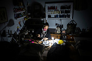 Rose Turner of Rose Alteration cuts elastic as a light illuminates the clothes she is altering during a power outage in her shop in downtown Placerville on Monday, Oct. 26, 2020.