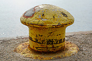 Yellow rusted bollard on a wharf