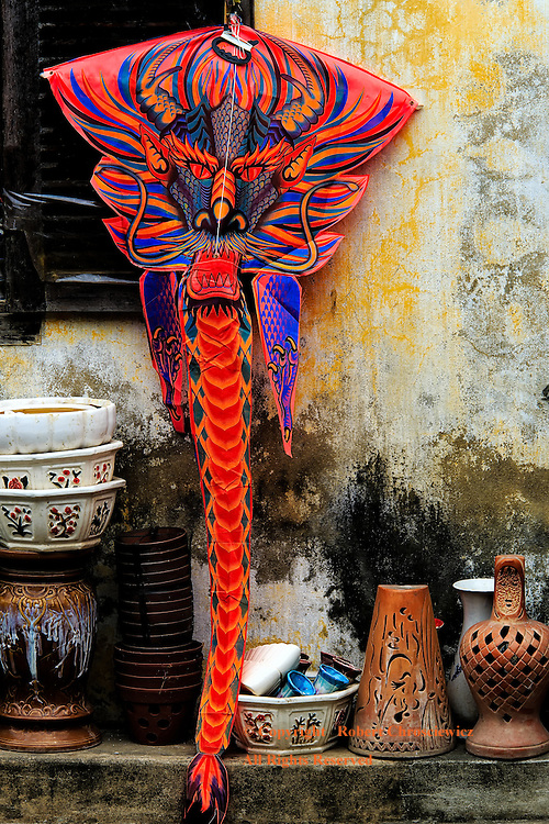 Dragon Kite: A bright red dragon kite rests pinned to a wall along with other household items, Hoi An Vietnam.