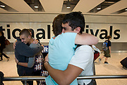 "Mothers and sons hug emotionally in the international arrivals hall of Heathrow Airport's Terminal 5 airport. Three families have gathered to meet their respective sons who have been travelling around the world during their university gap year sabbatical trip of a lifetime. With balloons and banners amid the hectic concourse where other relatives greet their loved-ones after months away from home on their adventures. This is a tradition practised across the world's airports where families are separated by the need to travel or work in other countries and the emotion of meeting again after long absences is always hard. From writer Alain de Botton's book project ""A Week at the Airport: A Heathrow Diary"" (2009)."