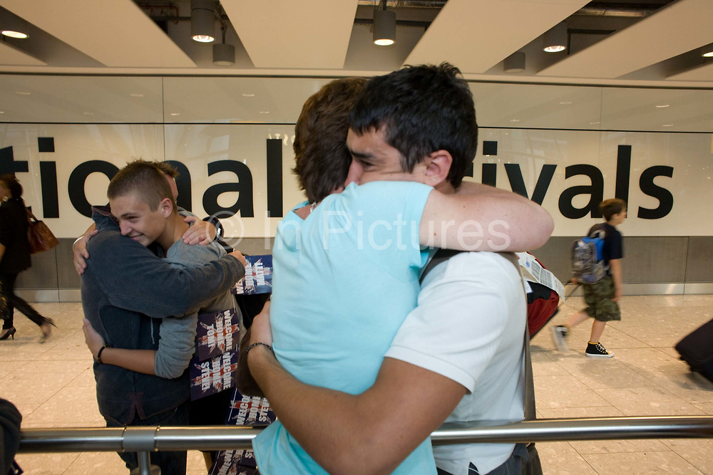 """Mothers and sons hug emotionally in the international arrivals hall of Heathrow Airport's Terminal 5 airport. Three families have gathered to meet their respective sons who have been travelling around the world during their university gap year sabbatical trip of a lifetime. With balloons and banners amid the hectic concourse where other relatives greet their loved-ones after months away from home on their adventures. This is a tradition practised across the world's airports where families are separated by the need to travel or work in other countries and the emotion of meeting again after long absences is always hard. From writer Alain de Botton's book project """"A Week at the Airport: A Heathrow Diary"""" (2009)."""