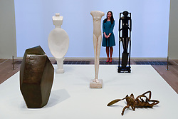 """© Licensed to London News Pictures. 08/05/2017. London, UK. A staff member stands with (L to R) """"Cube"""", 1933-34; """"Woman with her Throat Cut"""", 1932; """"Walking Woman (I)"""", 1932; """"Spoon Woman"""", 1927 and """"Invisible Object (hands holding the void)"""", 1934-35.  Preview of the UK's first major retrospective of Alberto Giacometti for 20 years at Tate Modern.  The exhibition runs 10 May to 10 September 2017. Photo credit : Stephen Chung/LNP"""