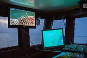 """A World War Two mine caught in fishing nets appears on a television mounted above marine navigation equipment,  installed in the cabin of a fishing boat. Hythe Bay, the English Channel, UK.<br /> Luke skippers his boat alone, to keep him company during the trip he has installed a TV. The journey begins with the opening scene of a Bond film where a Trawler boat nets a mine. """"I've caught a few of those in my time"""" say Luke as he navigates around mines, shipwrecks and WWII planes.  Luke is a Folkestone based fisherman out trawling for a 12 hour night shift on a fishing trip in his boat Valentine (FE20), Hythe Bay, the English Channel, UK. (photo by Andrew Aitchison / In pictures via Getty Images)"""