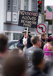An unidentified man who apparently has had enough of Kenyan runners constantly winning the event, holds a sign forbidding them from turning from Divisidero onto Fell Street, at the 107th running of the Bay to Breakers, Sunday, May 20, 2018, in San Francisco. (Photo by D. Ross Cameron)