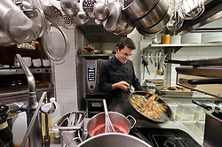 """Cologne, Germany, Jan. 2012 - Peter Foltynowicz, head chef at Nada, preps for the evening dinner service. Considering its location on a quiet, residential lane and a name that echoes the Spanish word for nothing, the lounge-like restaurant Nada might be accused of setting low expectations, only to demolish them once the inventive, playful cooking  a porcini soup disguised as a cappuccino, or """"Unctuous"""", slow-cooked roast beef and root vegetables in a gingery barolo glaze  hits the table. Considering the flash-bang culinary pyrotechnics and stellar service, prices  with main courses hovering around 25 euros, and four-course set menus at 54 euros  also seem (almost) understated (Cleverstrasse 32; 49-221-888-999-44; nada-koeln.de). (Photo © Jock Fistick)."""