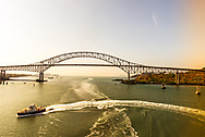 A boat leaves an arc in the water before the Bridge of the Americas, originally known as the Thatcher Ferry Bridge. It spans the Pacific entrance to the Panama Canal.