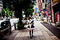 A worker from a Handmaid Cafe walks along the street in the Ginza District of Tokyo, Japan.