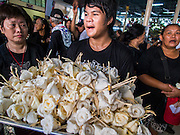 28 APRIL 2014 - BANGKOK, THAILAND: Mourners with dried flowers at the funeral for Kamol Duangphasuk, 45. Kamol was a popular poet who wrote under the pen name Mai Nueng Kor Kunthee. Kamol had been writing since the 1980s and was an outspoken critic of the 2006 coup that deposed Thaksin Shinawatra. After the 2010 military crackdown against the Red Shirts he went into temporary self imposed exile fearing for his safety. After he returned to Thailand he organized weekly protests against Thailand's Lese Majeste laws, which he said were being used to stifle dissent. Kamol was shot and murdered on April 23. The assailants are still at large but the murder is thought to be political.     PHOTO BY JACK KURTZ