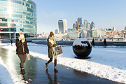 People walk to work on the south bank in front of City of London skyscrapers after snow has fallen overnight in London, England on February 28th, 2018. Freezing weather conditions dubbed the Beast from the East have brought snow and sub-zero temperatures to the UK.