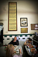 People eating pizza at the Antica Pizzeria de Michele, Naples, Italy.