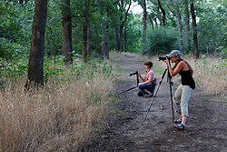 Photographers in upland forest, John F. Burke Nature Preserve, Texas, USA