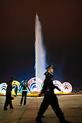 "A police officer walks past a grand lights and fountain show near the artificial lake in Kangbashi New District of Ordos City, Inner Mongolia, China on 16 August, 2011. With an investment of over 161billion USD from the local government and revenue from the region's rich coal deposits, enough buildings have risen on the site of an old desert village to hold at least 300,000 residents, complete with ultra modern facilities and grand plazas. The district however is less than 10% occupied, dubbed the ""ghost city"", Kangbashi epitomizes China's real estate bubble and dangers in mindless investment fueled economic  growth. In 2011, the real estate price of Ordos city has dropped over 70%."