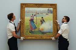© Licensed to London News Pictures. 29/01/2020. London, UK. Technicians hang Camille Pissarro's painting titled Gelée Blanche, Jeune Paysanne Faisant Du Feu (est £8m to £12m) at the preview of Sotheby's Impressionist, Modern and Surrealist art sales. The auction will take place at Sotheby's in central London on 4 and 5 February 2020. Photo credit: Dinendra Haria/LNP