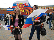 Junge Frauen mit russischen Flaggen vor der für die Militärparade aufgebauten Tribüne und monumentalen Dekoration auf dem Roten Platz am Tag der großen Siegerparade.<br /> <br /> Young women with Russain flags infront of the big tribune and monumental decoration prepared for the Military Parade at Red Square during the day of the Victory Parade in Moscow.