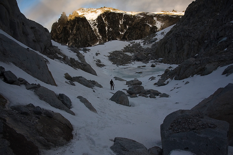 Climber Obadiah Reid traverses a snow covered alpine basin near Asgaard Pass as the sun sets on nearby peaks, Alpine Lakes Wilderness, Washington.