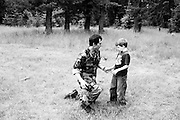 Cody Hoyt from Couer d'Alene, Idaho consoles his son after he finishes a nearby live fire training exercise during a weekend-long event at a Civilian Conservation Corps. camp near Priest River, Idaho...Hoyt explained that his son has never been fond of loud noises, but he is slowly trying to get him more accustomed to firearms.