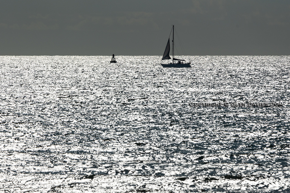 In brilliant sparkling sunshine a single yacht starts furling the jib on approach to the harbour. The sea was warm but the wind cooler than of late, a feeling of Autumn creeping in as Summer seeps away.