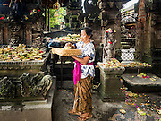 11 OCTOBER 2016 - UBUD, BALI, INDONESIA: A woman makes offerings as she walks through the Hindu temple in the market in Ubud. The temple in the market is very busy during the midmorning hours, when market vendors come to pray. The morning market in Ubud is for produce and meat and serves local people from about 4:30 AM until about 7:30 AM. As the morning progresses the local vendors pack up and leave and vendors selling tourist curios move in. By about 8:30 AM the market is mostly a tourist market selling curios to tourists. Ubud is Bali's art and cultural center.      PHOTO BY JACK KURTZ