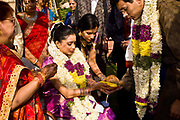Hindu bride, Shweta Singhal, sits on her father's lap as she hold in her hands a coconut and banana, as a priest recites verses meant to purify the bride, after which the father will give his daughter away to the bride groom ( newly-wed husband) as a gift. Shweta is surrounded here by her most immediate family and is a highly emotionally charged moment as it symbolises the abandonment of her caste to adopt her husband's,  Neemrana Fort Palace, Rajasthan, India.