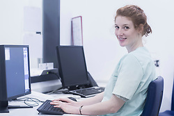 Smiling nurse working on computer while siting at nurse station