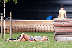 © Licensed to London News Pictures. 07/06/2021. London, UK. A woman sunbathes during sunny weather in St James's Park in South Central London. Temperatures are expected to rise with highs of 24 degrees forecasted for parts of London and South East England today . Photo credit: George Cracknell Wright/LNP