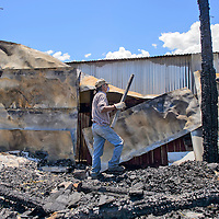 """Ed Johnson helps cleanup the aftermath of a house fire on Tuesday in the Gamerco neighborhood. Johnson was helping fix up Dina Ponce house following the fire that happened this weekend, """" I don't know half of these people, they just came and helped us get back on our feet"""" Ponce said."""