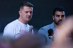 London, UK. 14 May, 2019. Former English Defence League leader Tommy Robinson (seen here with Avi Yemini of Rebel Media) watches his supporters manhandle a cameraman away as he makes a speech criticising the media outside the Old Bailey following a hearing during which two High Court judges declared that fresh proceedings may be brought against him for an alleged contempt of court over the filming of people involved in a criminal trial.