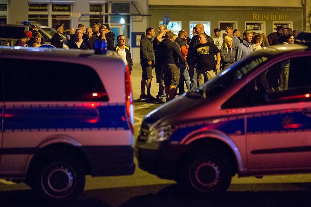 """Ca. 300-400 """"besorgte Bürger"""", Nazis, Rechte und Hooligans demonstrieren in der sächsischen Stadt Bautzen auf dem Kornmarkt gegen Flüchtlinge. In den letzten Tagen gab es auf dem Platz im Zentrum der Stadt Auseinandersetzung, in deren Folge ca. 80 Rechte 20 unbegleitete minderjährige Flüchtlinge durch die Stadt jagten, mehrerer Flüchtlinge wurden dabei verletzt. Eine antirassistische Kundgebung von ca. 40 Personen, die gegen die Gewalt gegen Flüchtlinge protestierten, kann nur unter starkem Polizeischutz stattfinden. Eine Gruppe rechter Demonstranten versuchte die linke Kundgebung anzugreifen, dabei kam es zu vereinzelten Flaschenwürfen, ein Kameramann wurde angegriffen. Im Bild: Polizisten halten Rechte von der antirassistischen Kundgebung fern. <br /> <br /> [© Christian Mang - Veroeffentlichung nur gg. Honorar (zzgl. MwSt.), Urhebervermerk und Beleg. Nur für redaktionelle Nutzung - Publication only with licence fee payment, copyright notice and voucher copy. For editorial use only - No model release. No property release. Kontakt: mail@christianmang.com.]"""