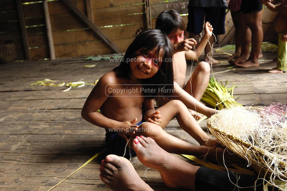 Ecuador, May 9 2010: Young Huaorani girls make string. Copyright 2010 Peter Horrell