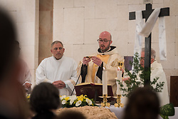 20 April 2019, Jerusalem: Father Bernard (centre), deacon Bassam Ghattas (left) and Father Najeeb (right) prepare for Holy Communion, as the congregation gathers for Holy Saturday service at Saint James' Church in Beit Hanina, Jerusalem.