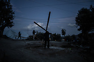 A man carrying two wooden poles is seen walking late in the evening in Moria camp. Security situation is critical during dark hours, many have been victims of violences , robberies and stabbing.. About 20000 are living in a makeshift camp nearby the city of Moria on the island of Lesbos in miserable conditions, most of the without water, electricity nor sanitary facilities.  Federico Scoppa