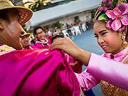 "14 JANUARY 2015 - BANGKOK, THAILAND: Participants in the 2015 Discover Thainess Parade finish each other's costumes. The Tourism Authority of Thailand (TAT) sponsored the opening ceremony of the ""2015 Discover Thainess"" Campaign with a 3.5-kilometre parade through central Bangkok. The parade featured cultural shows from several parts of Thailand. Part of the ""2015 Discover Thainess"" campaign is a showcase of Thailand's culture and natural heritage and is divided into five categories that match the major regions of Thailand – Central Region, North, Northeast, East and South.     PHOTO BY JACK KURTZ"