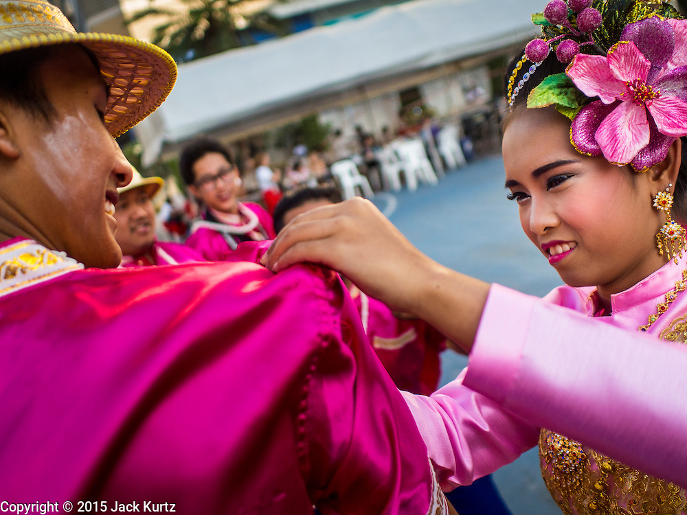"""14 JANUARY 2015 - BANGKOK, THAILAND: Participants in the 2015 Discover Thainess Parade finish each other's costumes. The Tourism Authority of Thailand (TAT) sponsored the opening ceremony of the """"2015 Discover Thainess"""" Campaign with a 3.5-kilometre parade through central Bangkok. The parade featured cultural shows from several parts of Thailand. Part of the """"2015 Discover Thainess"""" campaign is a showcase of Thailand's culture and natural heritage and is divided into five categories that match the major regions of Thailand – Central Region, North, Northeast, East and South.     PHOTO BY JACK KURTZ"""